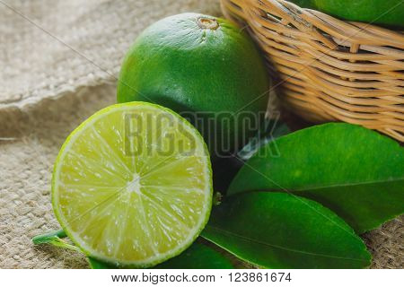 Selective focus to slice fresh lime and leaf lime on sack background.Many lime in the wood basket.