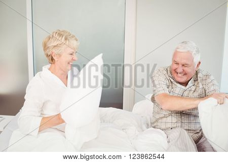 Happy senior couple having pillow fight in bed at home