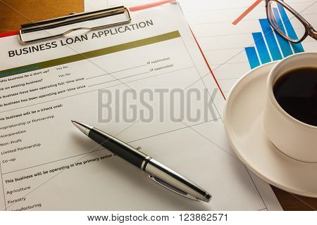 selective focus pen Business loan application form summary chart black coffee paper clip on wood background.