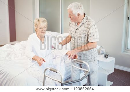 Senior man assisting ill woman in getting up from bed in room