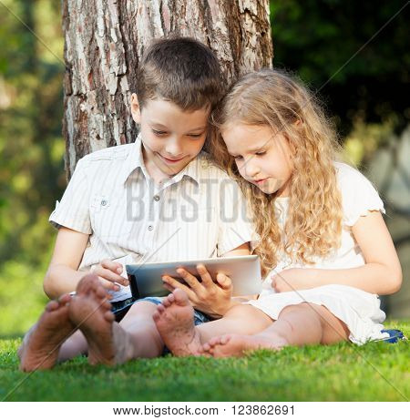Children with tablet pc outdoors. Girl and boy on grass with computer