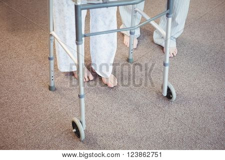 Low section of elderly man and woman with walker on carpet in bedroom
