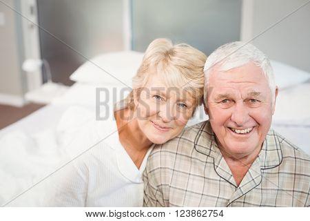Portrait of happy senior couple in nightwear on bed