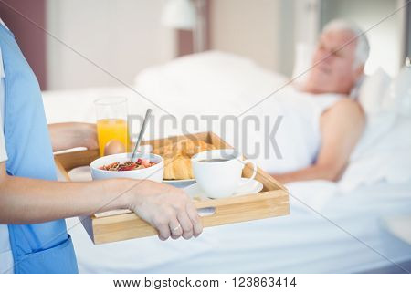 Midsection of nurse with breakfast in tray while senior man lying on bed