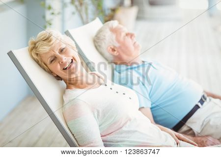 High angle view of senior couple relaxing on lounge chair at porch
