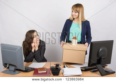 The Girl In The Office Happily Holding Bags And Looking At Colleague