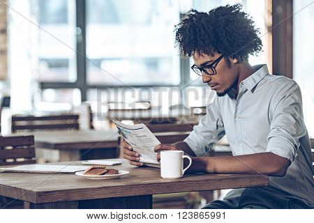 Fresh newspaper in the morning. Side view of young African man in glasses reading newspaper while sitting in cafe