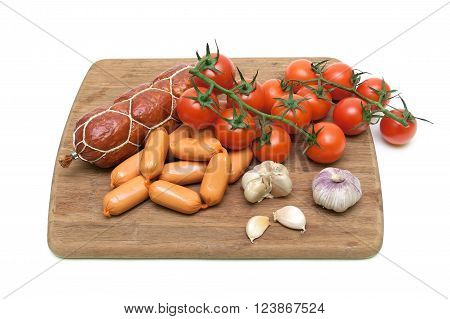 sausage and vegetables on a cutting board. white background - horizontal photo.