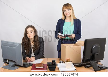 An Employee In The Office Happily Puts Things Out Of The Box Next To A Colleague
