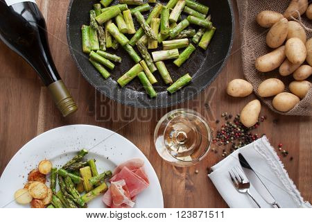 Green fried asparagus with ham potatoes and white wine