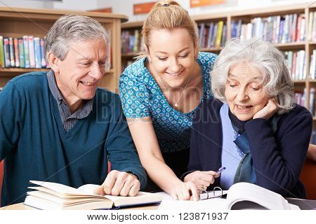 Mature Students Working With Teacher In Library