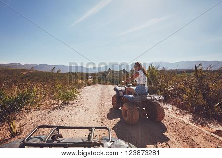 Young woman driving a quad bike on country road. Young woman on an all terrain vehicle in nature on a sunny day.