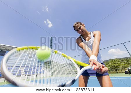 Beautiful female tennis player in action hitting a forehand