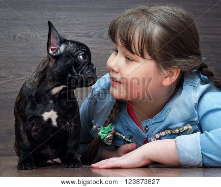 Dialogue child with a dog. The girl speaks with an English bulldog puppy