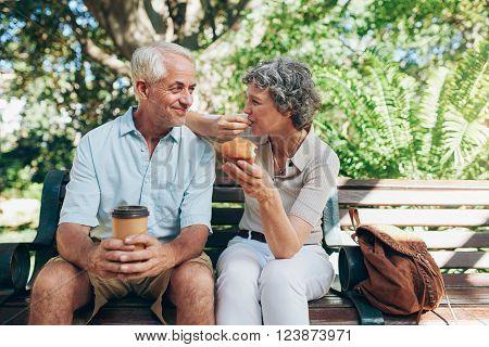 Loving Senior Couple Sitting On A Park Bench