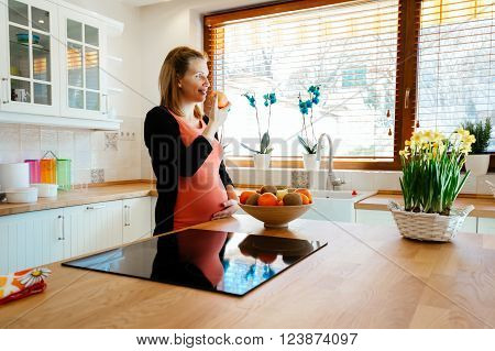 Pregnant woman eating fruit in kitchen and happily anticipating newborn