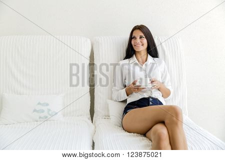Beautiful young happy woman sipping tea and relaxing
