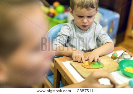 Creative young  handsome kid playing with dough