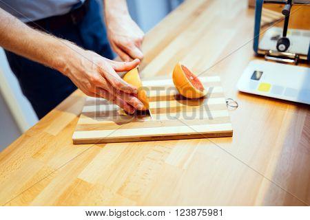 Man slicing orange in kitchen with knife