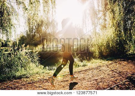 Fit woman jogging in park sorrounded by trees