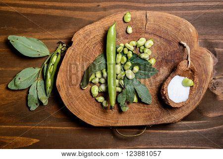 Fresh green beans seen from above on a rough wood floor brown color. Seasonings of Mediterranean cuisine: olive oil salt.