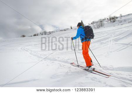 Man alone with ski mountaineering climb towards the summit