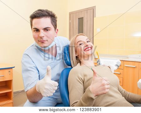 Confident male dentist and female patient showing thumbs up gesture