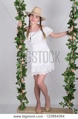 full-length Beautiful young leggy blonde in a little white dress and white cowboy hat on a swing, wooden swing suspended from a rope hemp, rope wrapped vine and ivy.