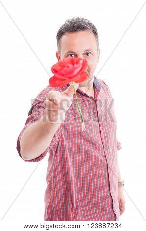 Man throwing a red flower to the camera as a romantic gesture