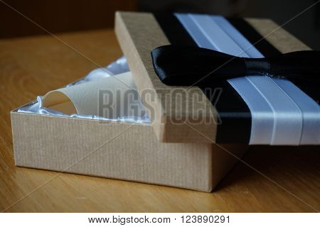 Luxurious gift box with a white and black velvet ribbons on the top