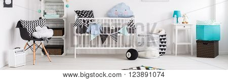 Baby room in black white and blue with simple cot and stylish decorations