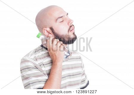 Man cooling his neck with cold water in plastic bottle as summer season heat concept