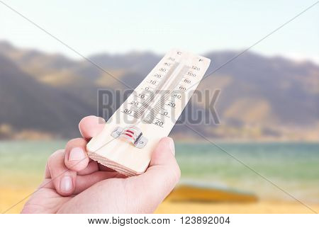 Hand Holding Thermometer On Sunny Day Background