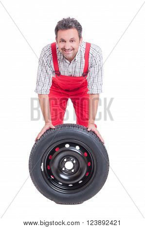 Smiling Mechanic And Car Wheel With Black Tire