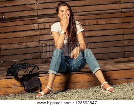 Young female model laughing at photo shooting on outdor wooden background