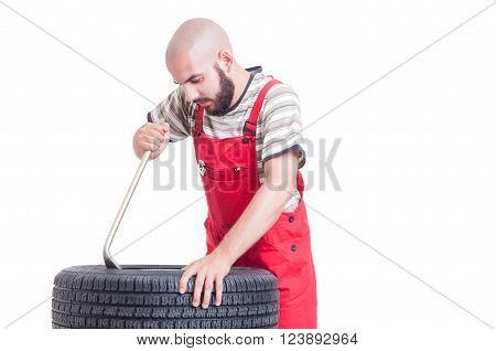 Mechanic Changing Tire Using Crowbar