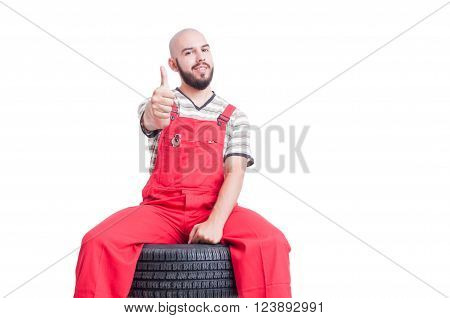 Young Mechanic Sitting On Car Wheel And Showing Like