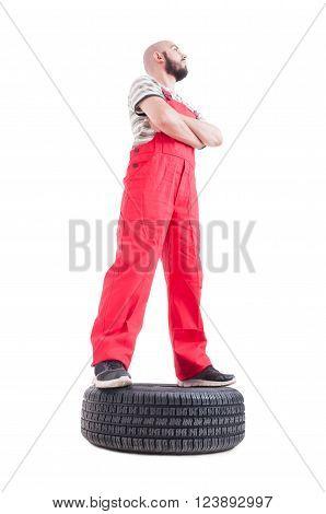 Hero Shot Low Angle Of Mechanic Standing On Car Wheel