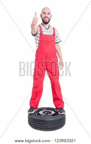 Mechanic Standing On Top Of Car Wheel And Showing Like