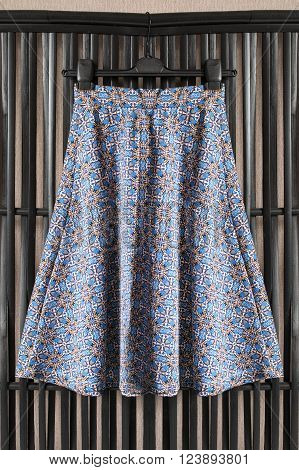 Silk colorful skirt on clothes rack over black wooden screen