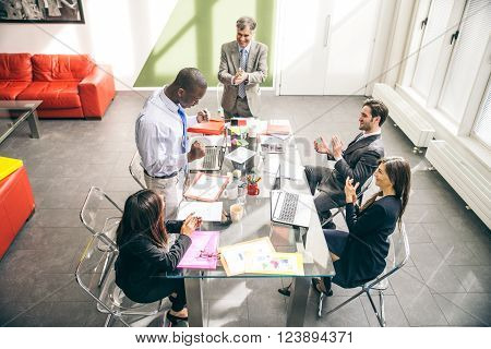 Business team having a meeting in a office afro-american man exulting and his colleagues clapping hands - Successful businessman getting a promotion at work