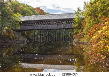 A wooden covered bridge supports foot traffic across the Contoocook River at Henniker, New Hampshire.
