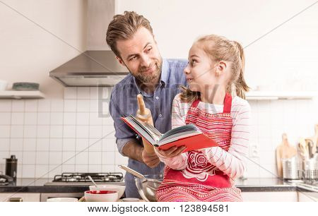 Caucasian father and daughter having fun while getting ready to bake cookies in the kitchen - happy family time.