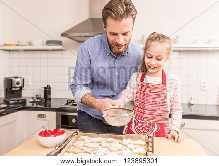Smiling caucasian father and daughter sprinkling powdered sugar on homemade cookies. Baking - happy family time in the kitchen.
