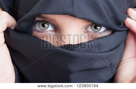 Close-up with beautiful islamic woman eyes and face covered by black burka