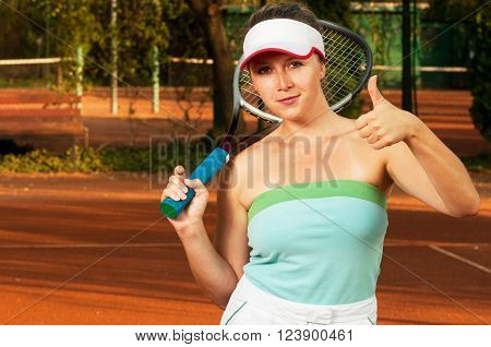 Female tennis player showing like or thumb-up gesture and holding racket on shoulder