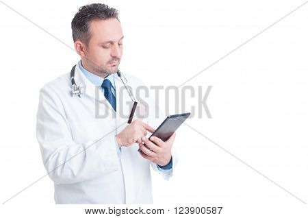 Doctor or medic using credit card and wireless tablet as online medical services secure payment concept