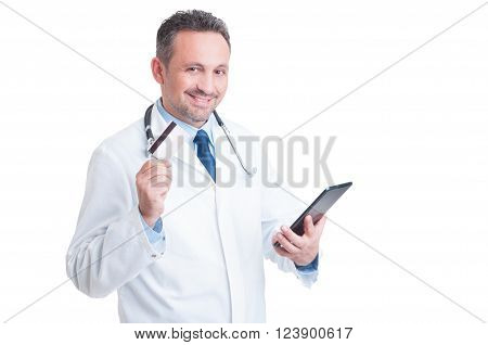 Doctor or medic holding credit card and wireless tablet as online medical services secure payment concept