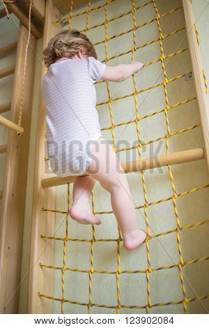 Baby kid playing sports and climbing the rope ladder