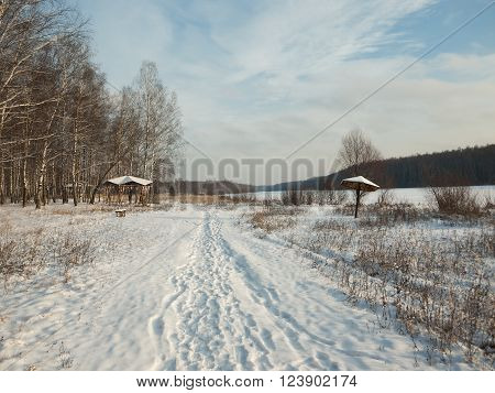 Winter path near the river and forest